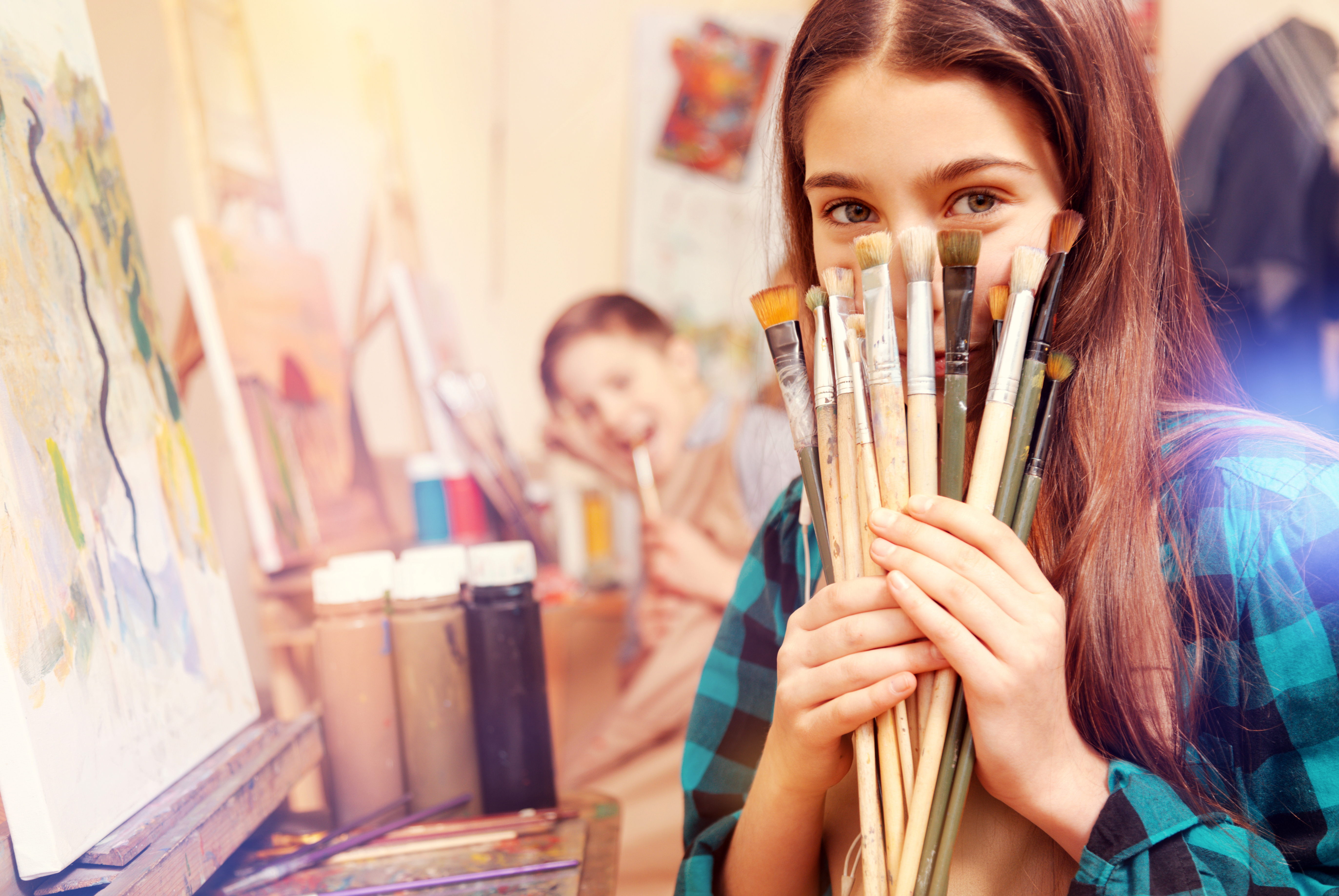 True little painter. Selective focus on a young lady of magical beauty hiding her face behind painting brushes while sitting at a painting easel and posing for the camera.