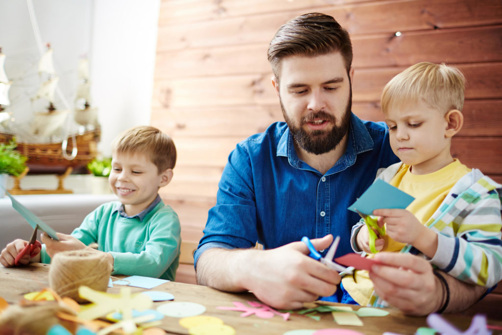 Young handsome male teacher and two little boys with scissors in hands cutting from colorful paper in art class